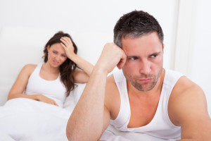 Frustrated Man Sitting On Bed In Front Of Young Woman